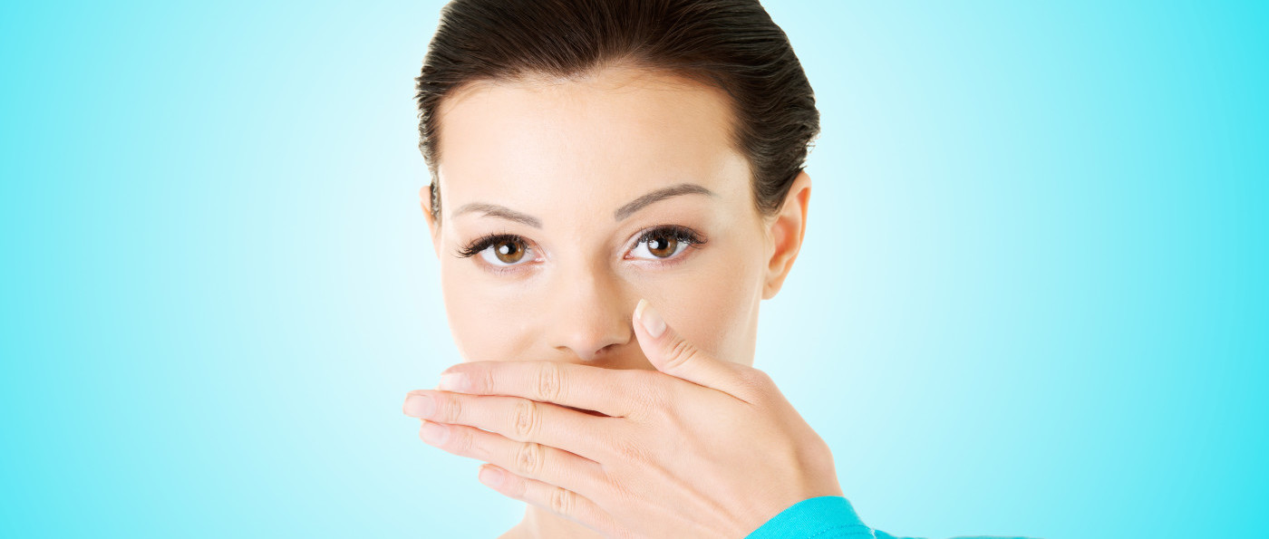 A woman covering her mouth to check bad breath with her hand.