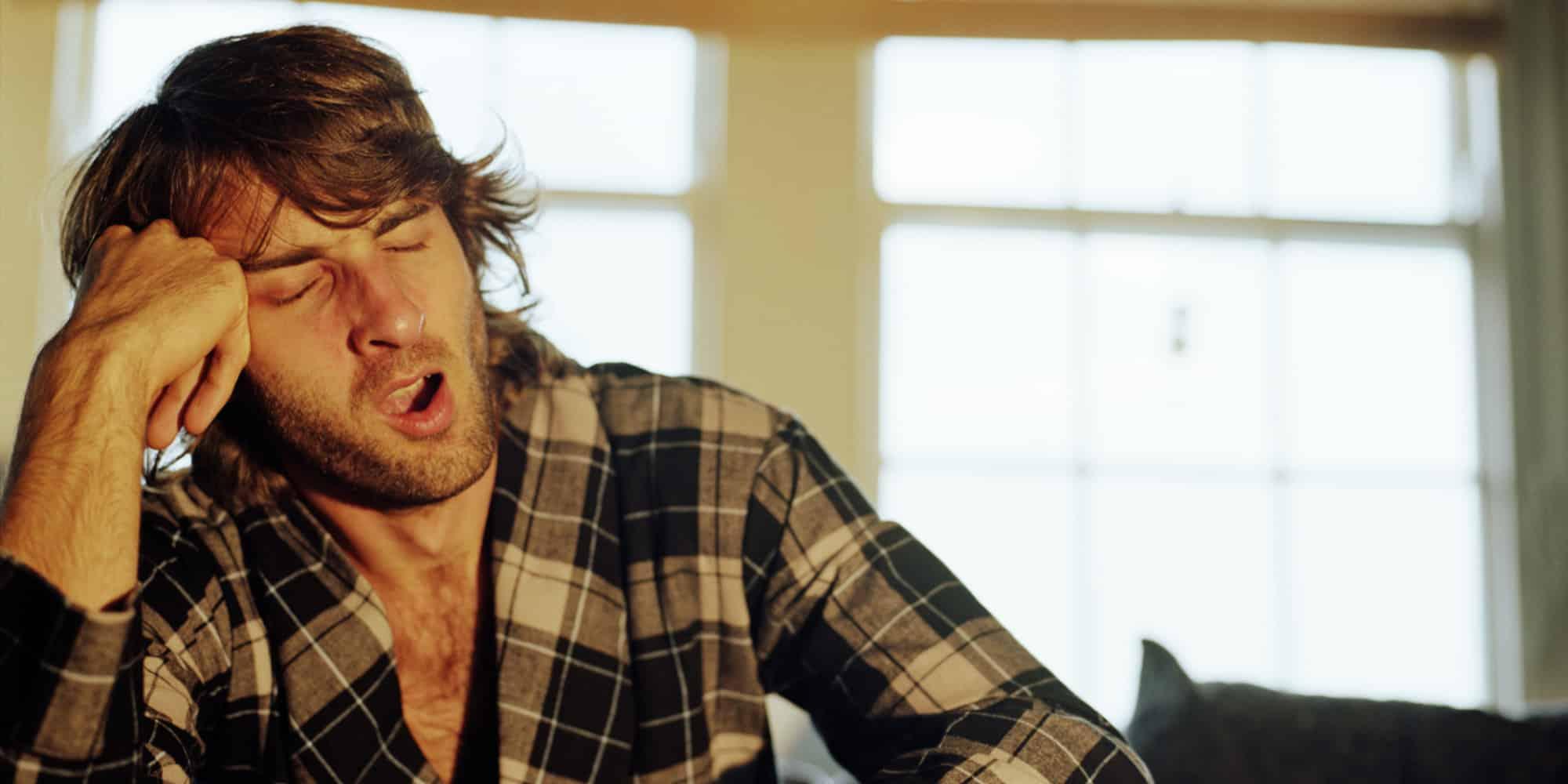 Man in bathrobe yawning, head resting on hand, eyes closed